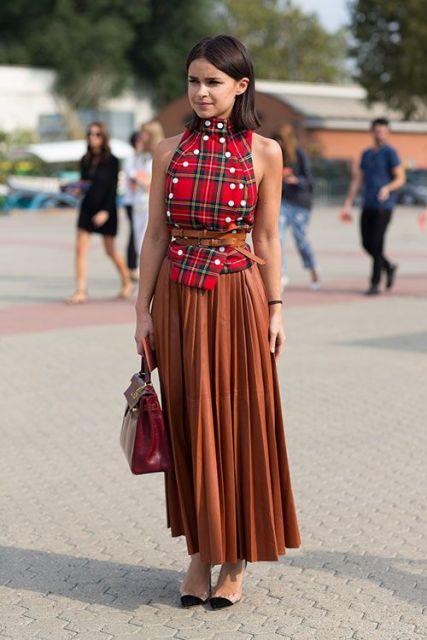 modelo usa saia caramelo, sapatinho, blusa xadrez e bolsa.