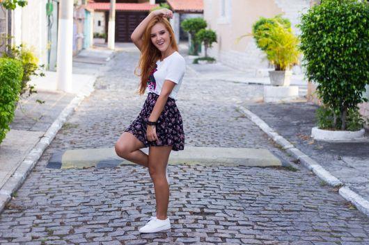 modelo usa saia florida curta com tenis e camiseta branca.