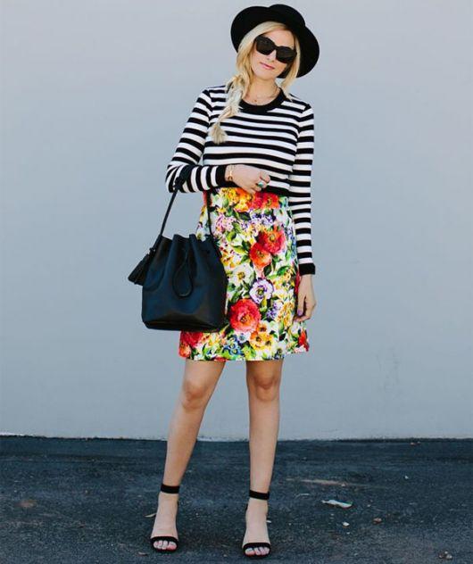 modelo usa saia florida colorida, blusa preta e branca manga longa e sandalia.