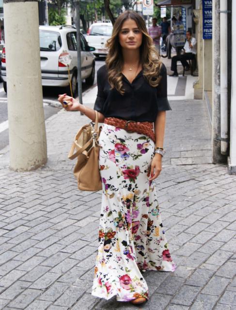 modelo veste saia florida branca, blusa preta e bolsa.