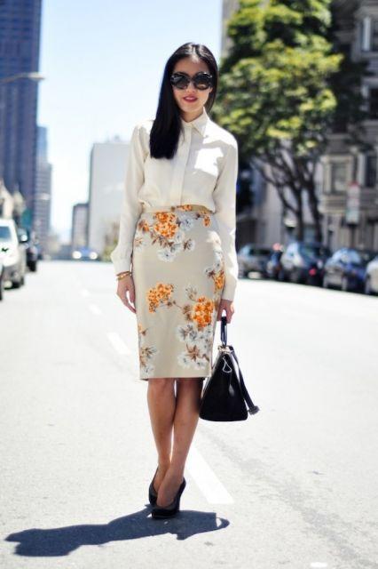 modelo usa saia florida com flores amarelas, camisa branca, bolsa e sapato preto.