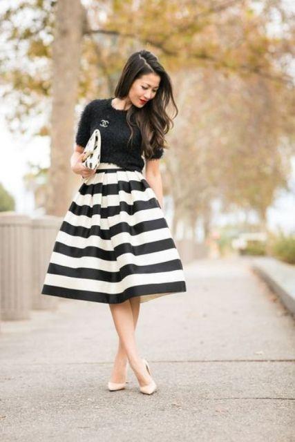 modelo usa saia midi rodada preta e branca, blusa preta e sapato nude.