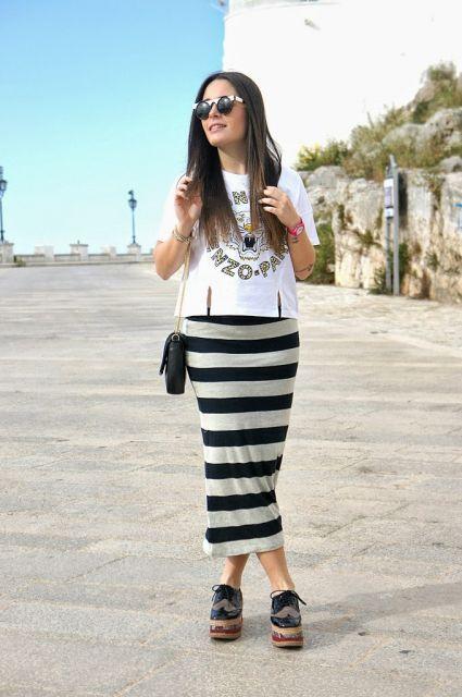 Modelo usa saia listarada de preto e branco midi, com sapato preto, bolsa e camiseta.