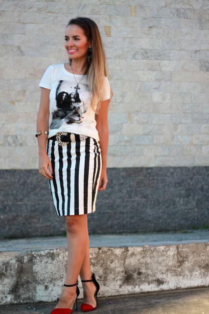 Modelo usa saia preta e branca listrada, camiseta preta e sandalia.