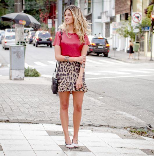 modelo usa blusa vermelha, saia de oncinha curta e scarpin.