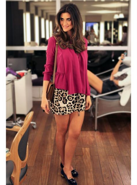 modelo usa saia de oncinha, blusa rosa e scarpin preto.
