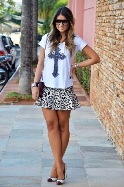 modelo usa camisetinha branca, saia de oncinha curta e scarpin.