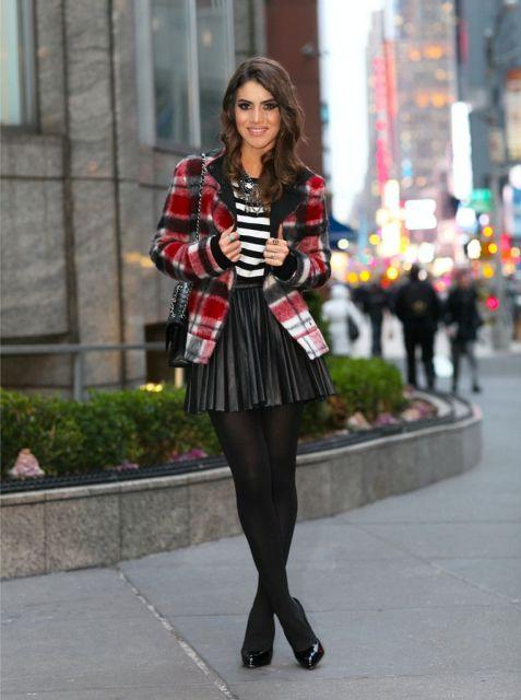 modelo usa saia preta de couro, meia preta, scarpin preto, jaqueta xadrez e blusa listrada de preto e branco.