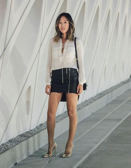 modelo usa saia preta, blusa branca, sandalia e bolsa.