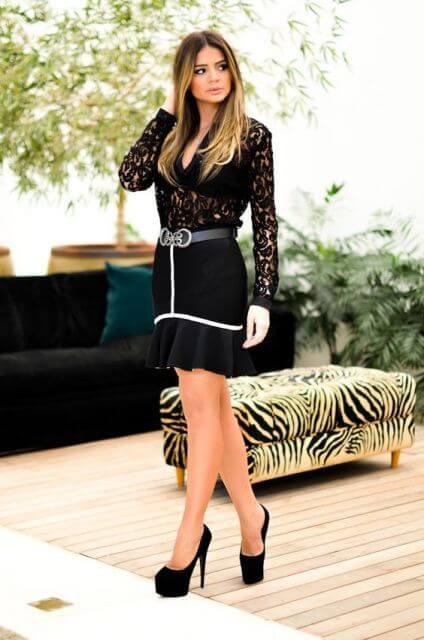 modelo usa saia preta, blusa de renda e sapato preto.