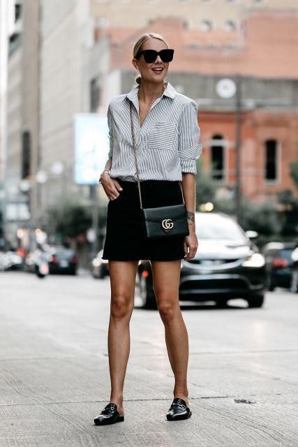 modelo usa chinelo, camisa e saia preta curta.