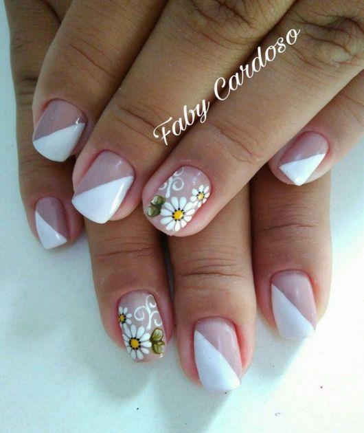 Unha decorada com branco e flores margaridas pequenas.