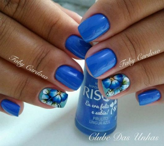 modelo com unhas pintadas de azul com desenhos de flores.