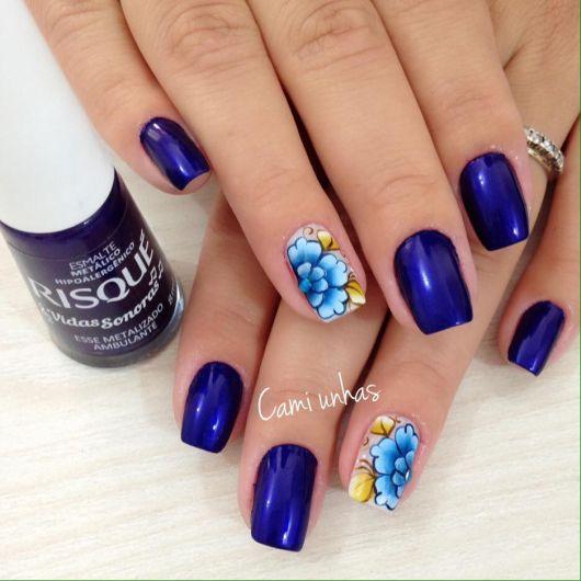 modelo mostra unhas pintadas na cor azul marinho com flores azul claro e folhas douradas.