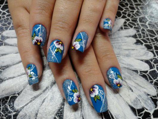 foto de maos com unhas decoradas na cor azul com flores brancas.