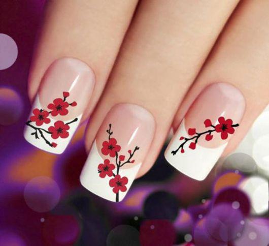 modelo mostra decoração de flores pequenas, vermelha com preto nas unhas.