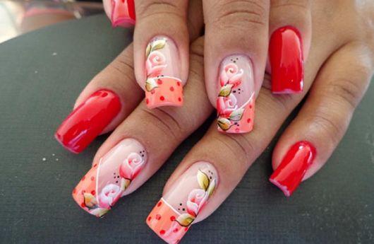 unhas decoradas com esmalte vermelho, flores e esmalte laranja.