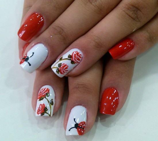 unhas decoradas com flores vermelhas por cima de esmalte vermelho e branco.