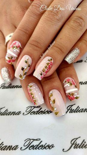 Unhas decoradas com flores cor de rosa.