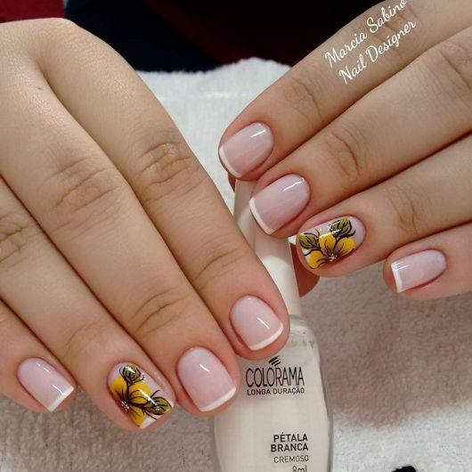 modelo com unhas francesinha fina com um dedo decorado com flores amarelas.
