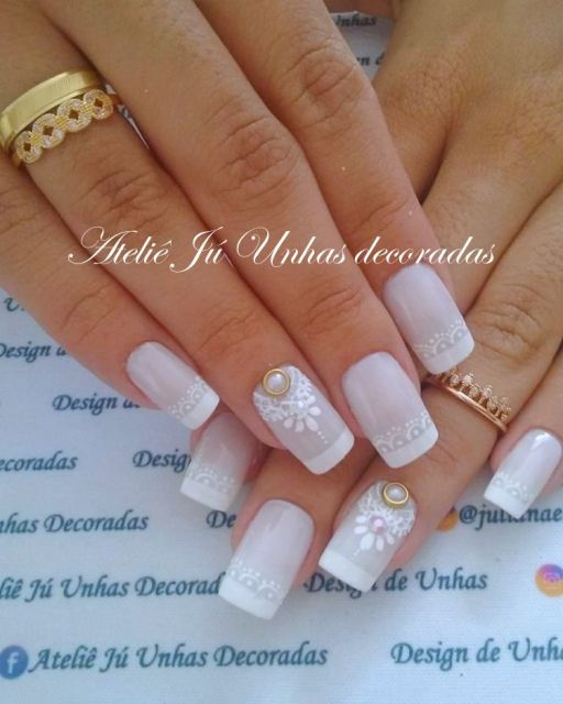 unhas decoradas com francesinha branca e flores na mesma cor.