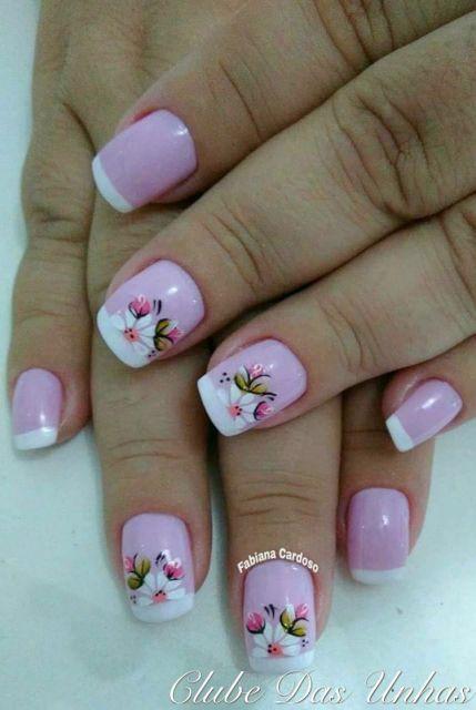 unhas cor de rosa com francesinha e flores brancas.