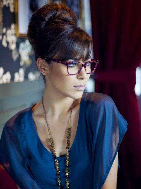 Mulher com blusa azul e óculos roxo.