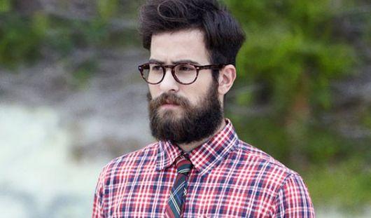 Homem com barba e camisa xadrez.