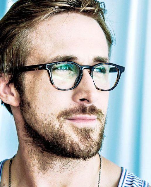 Ryan Gosling com óculos de armação escura.