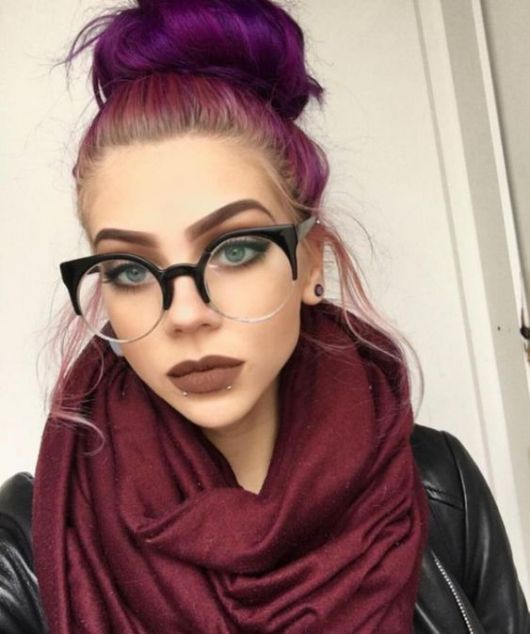 Mulher com cabelo rosa e óculos gatinha.