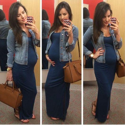 Gestante com vestido azul longo e jaqueta jeans.