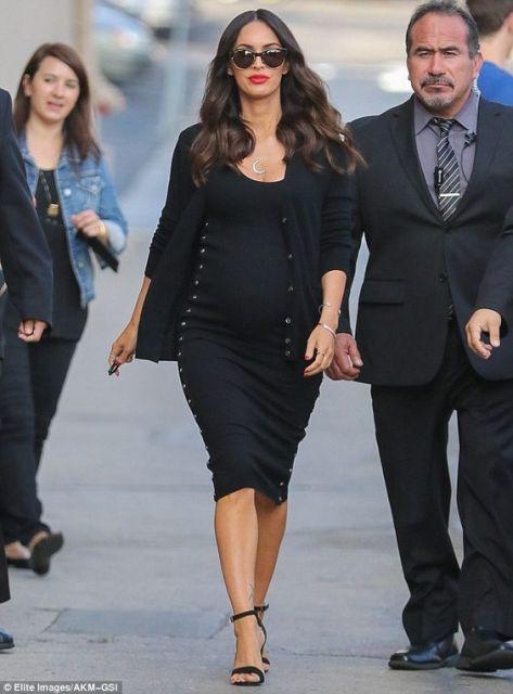 Megan Fox com vestido e casaco pretos.