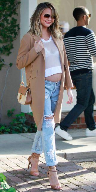 Chrissy Teigen com calça jeans destroyed e blusa transparente.