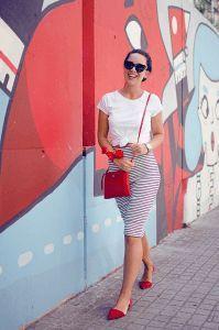 Mulher com saia listrada e camiseta branca.