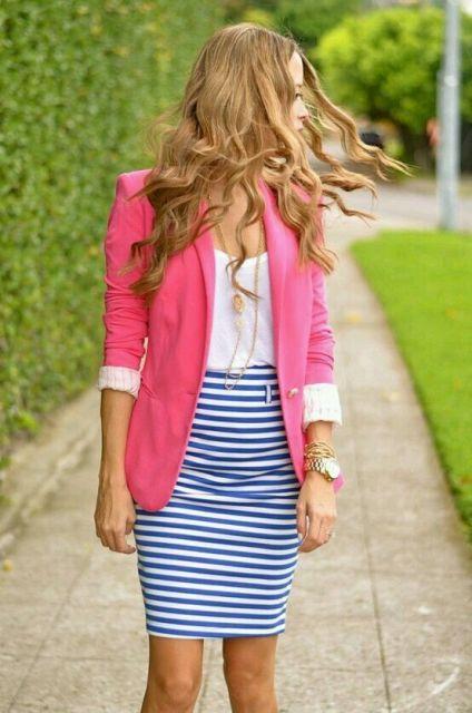 Mulher com saia listrada e blazer rosa.