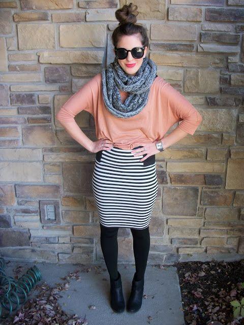 Mulher com saia lápis listrada, blusa rosa e meia calça.