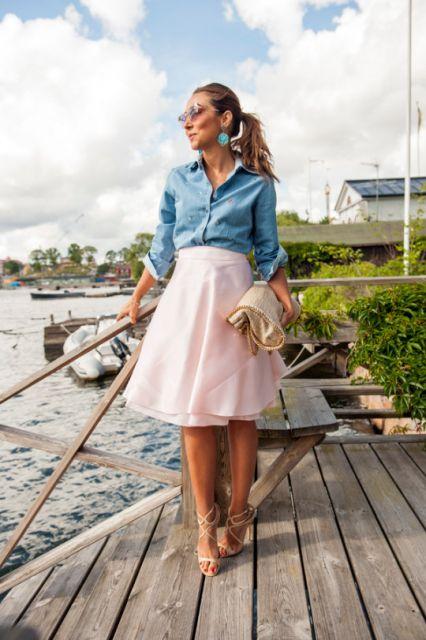 modelo usa saia rosa, camisa feminina jeans e sandalia nude.