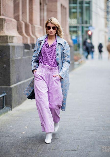 modelo usa calça pantalona roxa, camisa feminina na mesma cor e sobretudo jeans.