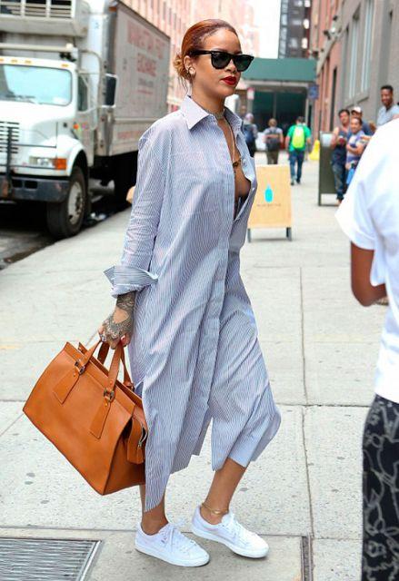 modelo usa camisa longa azul com tenis branco e bolsa laranja.