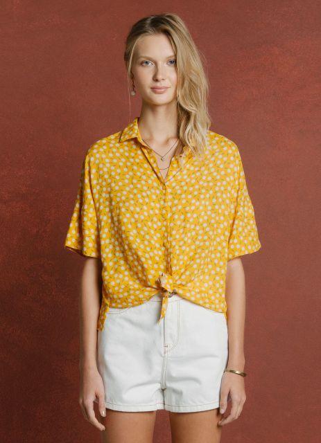 modelo usa bermuda branca e camisa feminina amarela.