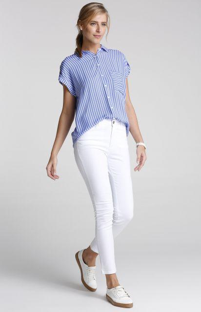 modelo usacalça branca, camisa azul e tenis.