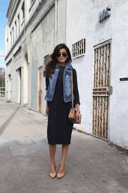 modelo usa vestido preto, colete jeans e scarpin nude.