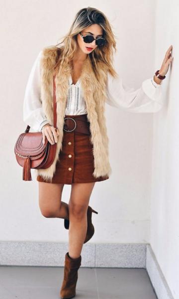 modelo usa saia marrom, camisa branca, colete de pelos nude, bolsa e botinha caramelo.