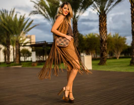 modelo usa saia suede, colete de franjas e bolsa estampada.