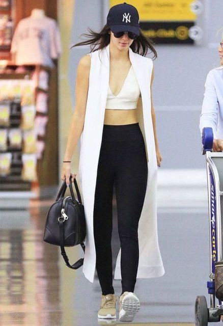 modelo usa colete branco, blusinha e corsario preta.
