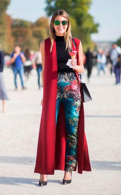 modelo usa calça estampada, blusa preta, scarpin preto e maxi colete vermelho.