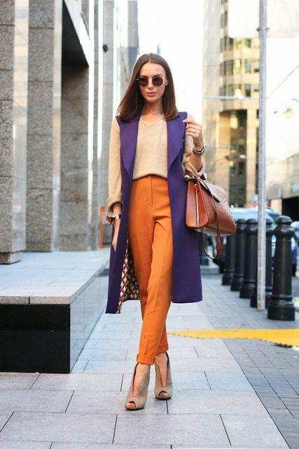 modelo usa calça laranja, blusa nude e colete roxo com sapato nude.