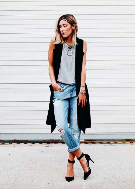 modelo usa colte longo preto, jeans e camiseta cinza.