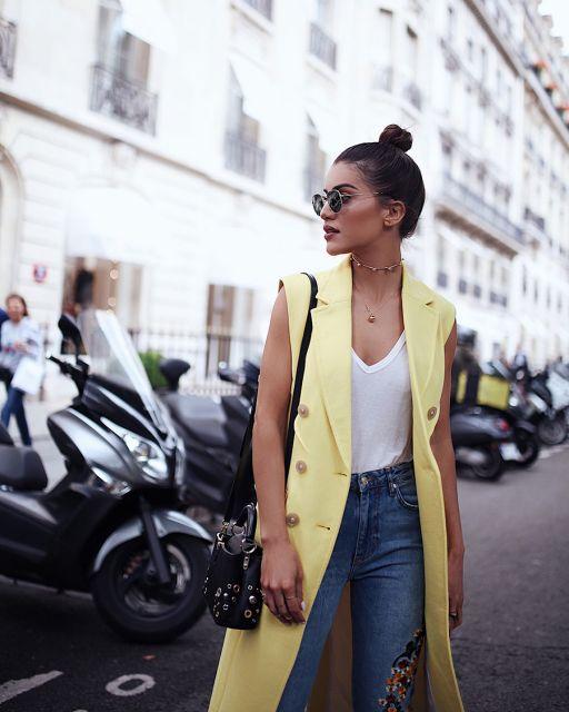 modelo usa colete amarelo, calça jeans e blusa branca.