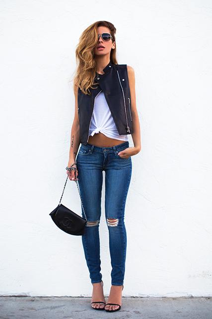 modelo usa calça jeans destruída, blusa branca, colete, bolsa preta e sapatilha.